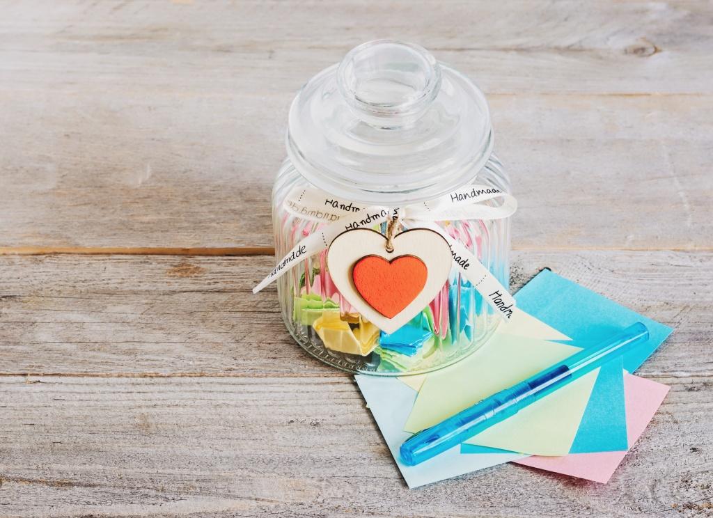 Pot de verre contenant des petits papiers colorés